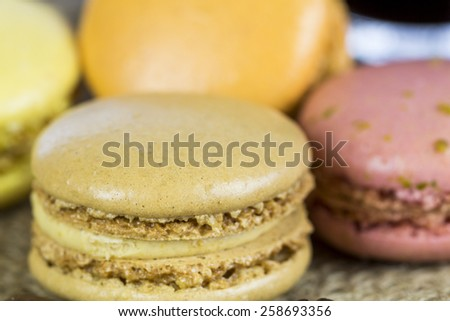 Batch of freshly baked colorful macarons made from egg white, coconut, almond and sugar and filled with ganache or butter cream, tilted angle view - stock photo
