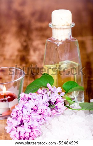 bath and spa items (oil, salt, lilac, candle) on wooden background - stock photo