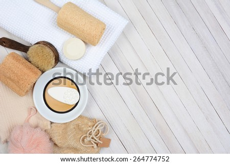 Bath and Spa still life. High angle shot of bathroom accessories including, towel, soap, loofah and sandals, on a rustic white wood surface. Items are set to the left side leaving room for your copy. - stock photo