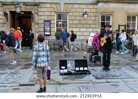BATH - AUG 9: An unidentified musician performs in the courtyard of Bath Abbey and the Roman Baths on Aug 9, 2014 in Bath, UK. Bath is a UNESCO world heritage city and popular tourist destination. - stock photo