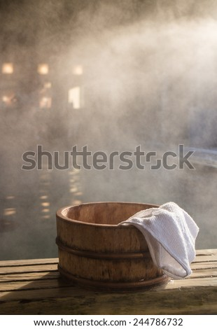 Bath bucket with a towel at blurred and fogged hot spring bath at Japanese onsen. Shot in the light of rising sun. - stock photo