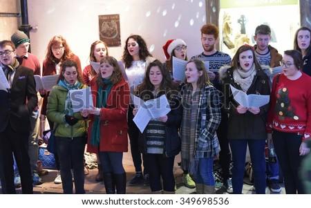 BATH - DEC 9: A choir sing carols at the Christmas Market in the streets surrounding Bath Abbey on Dec 9, 2015 in Bath, UK. The market is held annually in the historic Unesco World Heritage City. - stock photo