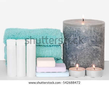 Bath or shower accessories on white background. Terry cloth towels, small plastic bottles, pastel color soaps, tea lights, and large wax pillar candle.