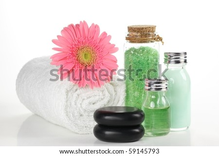 Bath salt,essential oil and towel over white. - stock photo