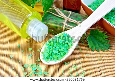 Bath salt in a spoon, homemade soap with twine, oil in the bottle, nettle, shampoo on a background of a bamboo napkin - stock photo