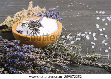 bath salt in bamboo bowl and dried lavender flowers on old black wood table - stock photo