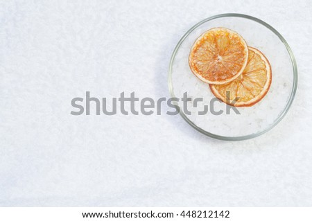 Bath salt in bowl  and dried orange slices on the towel. Overhead view