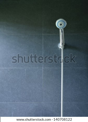 Bath shower on black tile wall - stock photo