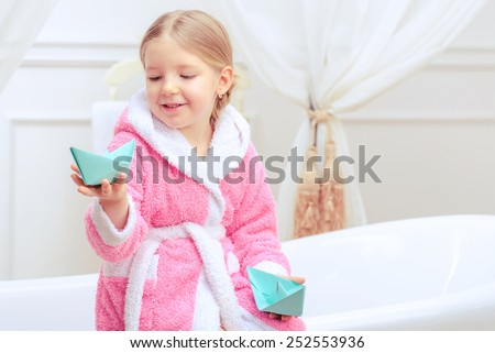Bath time is fun. Closeup image of a cute little girl in a pink bathrobe holding paper ships while sitting on a luxurious bathtub with happy face expression - stock photo