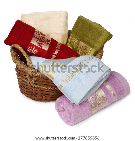 Bath towels of different colors in wicker basket on white backgrounds - stock photo