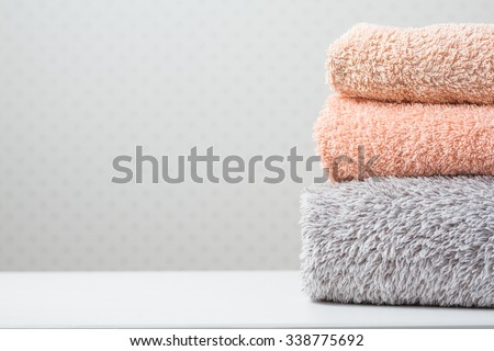 Bath towels of different colors on light background - stock photo