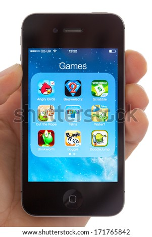 BATH, UK - JANUARY 17, 2014: Hand holding an Apple iPhone 4s which is displaying a selection of well known games including the best selling app Angry Birds. Shot in close-up with a white background. - stock photo
