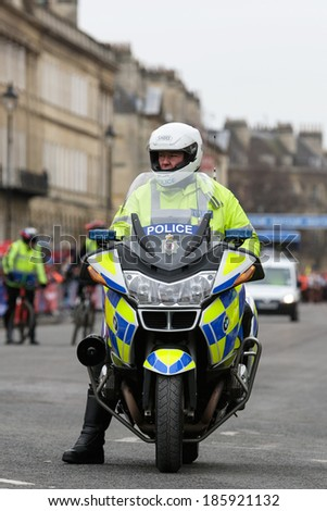 BATH, UK - MARCH 6: A motorcycle police officer from Avon and Somerset police waits to escort the runners at the 2011 Bath Half marathon on March 6, 2011 in Bath, UK. - stock photo