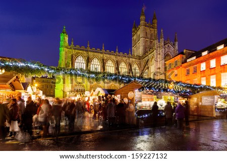 BATH, UK - NOVEMBER, 25: Bath Christmas market at night on 25th Nov 2011 with Bath Abbey in the background. During the festive period vendors sell from temporary wooden chalets in the city centre. - stock photo