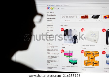 BATH, UK - SEPTEMBER 14, 2015: Close-up of the Ebay homepage displayed on a LCD computer screen with the silhouette of a man's head out of focus in the foreground.