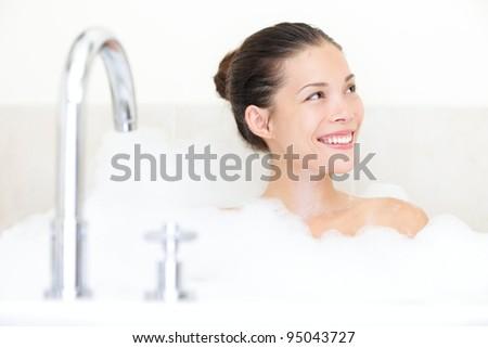 Bath woman enjoying bathtub with bath foam smiling happy. Mixed race Asian / Caucasian female model in bathroom. - stock photo