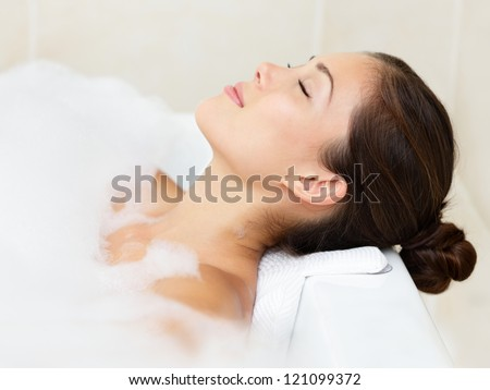 Bath woman relaxing bathing in bathtub with bath foam. Beautiful young mixed race Asian Caucasian female model in bathroom. - stock photo