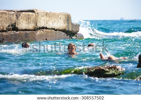 bathing children in a dangerous zone near stones in the sea - stock photo