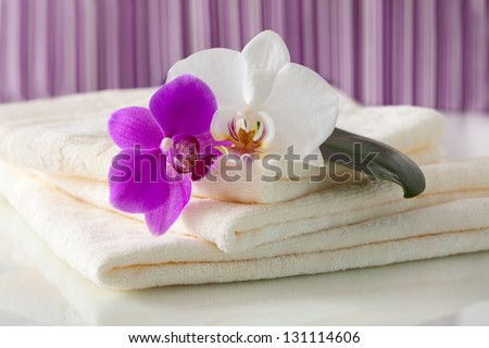 bathing towels and orchids on a light background - stock photo