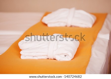 Bathrobes and duvet on bed in hotel - stock photo