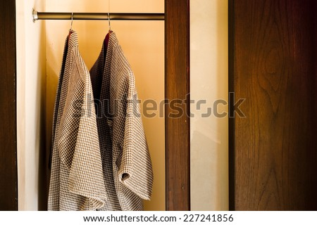 bathrobes hanging in wooden closet  - stock photo