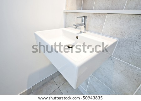 Bathroom detail ceramic wash basin and natural stone tiled walls in beige - stock photo