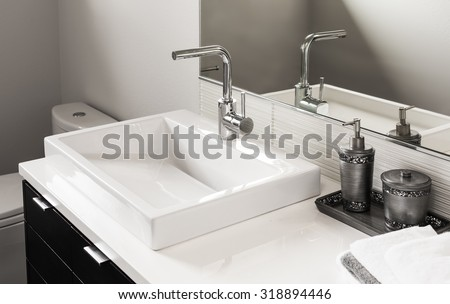 Bathroom detail in new luxury home: sink and faucet with partial view of toilet - stock photo