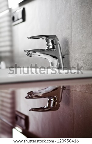 Bathroom faucet reflection on red board - stock photo