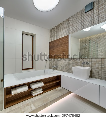 Bathroom in a modern style with light tiles on the left wall and floor. On the left there is a white bath with wooden niches with towels. On the right there is a white rack with white sink. Right wall - stock photo