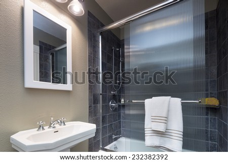 Bathroom in grey with glass shower and white framed mirror.  - stock photo
