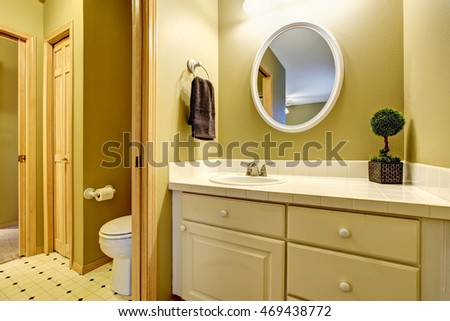 Bathroom interior in yellow tones with vanity cabinet and tile counter top. Northwest, USA