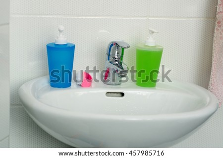Bathroom interior with white sink and faucet, two colorful spray bottle for detergent, cleaning products bottle, brush and towel/Close Up of Modern Bathroom Sink, tap and accessories  - stock photo