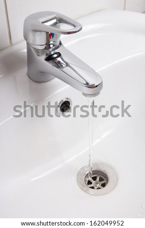 Bathroom interior with white sink and silver faucet - stock photo