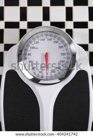 Bathroom Scale on Black and White Tile Floor - stock photo
