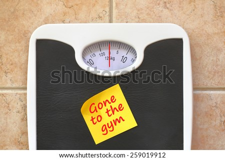 Bathroom scale with Go to Gym memo sticker. Diet and fitness concept - stock photo