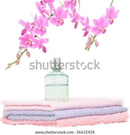 Bathroom set with three towels, a perfume bottle and a decorative pink orchid - stock photo