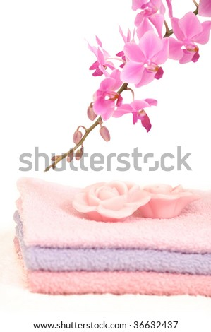 Bathroom set with three towels, two rose petal shaped pieces of soap and a decorative pink orchid - stock photo