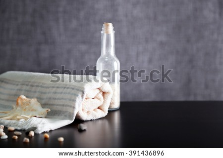 Bathroom set with towel, shell and glass bottle on grey background - stock photo