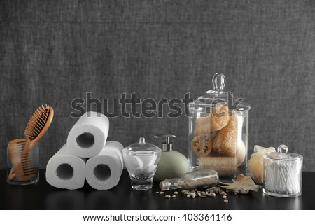 Bathroom set with wooden comb, paper towels and sponges on grey background - stock photo