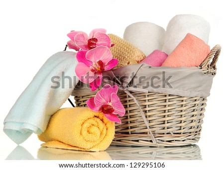 Bathroom towels folded in wicker basket isolated on white - stock photo