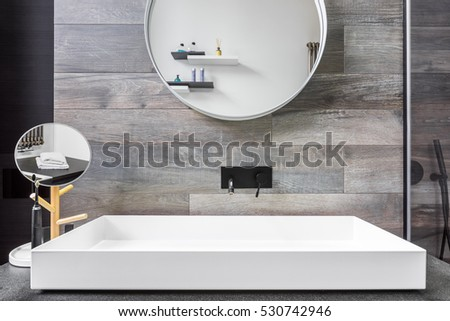 Bathroom with countertop washbasin, mirror and grey tiles