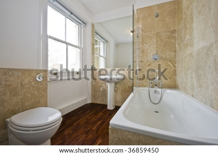 bathroom with light brown marble tiles and wooden floor