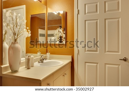 Bathroom with white door and orange accent paint - stock photo