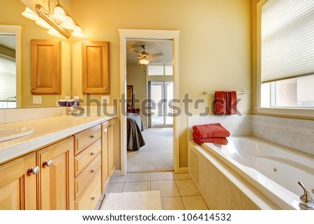 Bathroom with wood cabinets, tile floor and tub. - stock photo