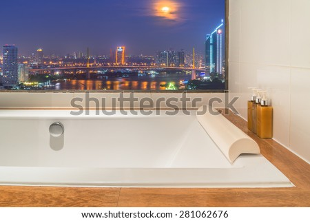 bathtub against huge window with city night view - stock photo