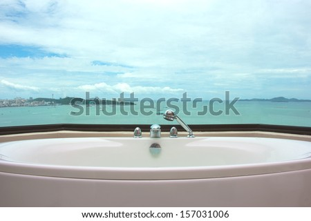 Bathtub in restroom on sea view background - stock photo