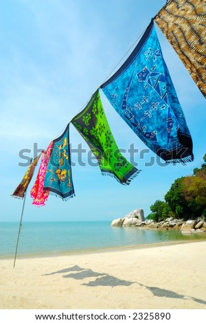 Batik is hanged at the beach. Batik is hand-dyeing clothes, is traditional handicraft in tropical country like Malaysia and Hawaii. - stock photo