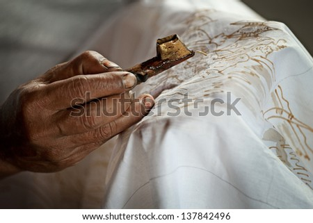 Batik painting on a white cloth process close up. Indonesia - stock photo