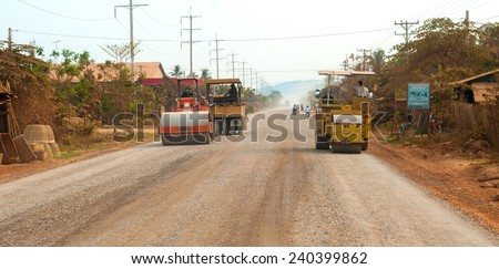 BATTAMBANG PROVINCE, CAMBODIA - FEBRUARY 19 2014: A road construction crew smooths down new gravel on a stretch of the main highway between Seam Reap (location of Angkor Wat) and Battambang. - stock photo