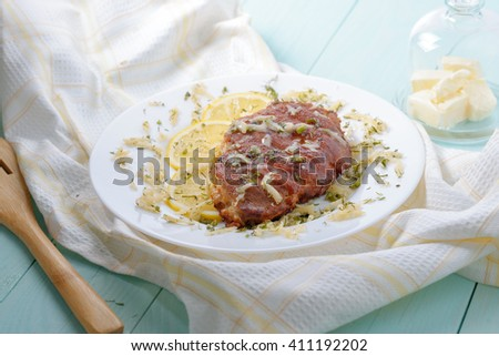 Battered chicken fillet with lemon and cheese. - stock photo